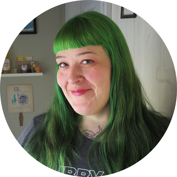 Photo of a women turned towards the camera. She is smiling and has long green hair and straight bangs.