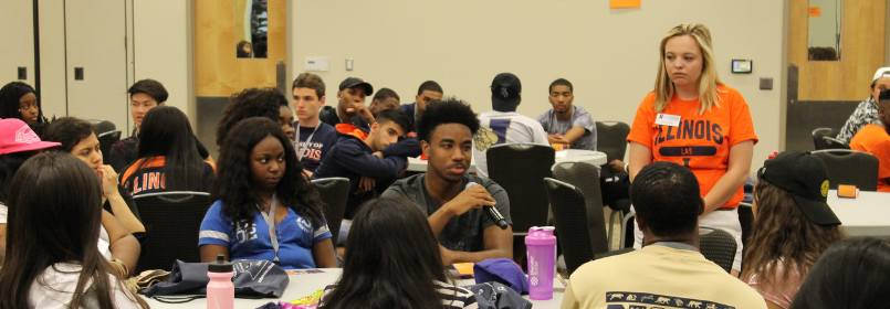 A man holds a microphone at a circular table while a room of college-aged indivuals look on.